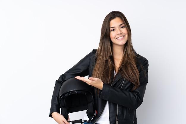 Jeune femme avec un casque de moto sur un mur blanc isolé, tendant les mains sur le côté pour inviter à venir