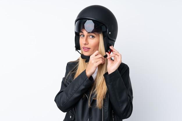 Jeune femme avec un casque de moto sur un mur blanc isolé