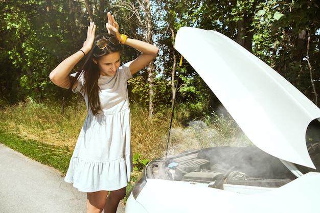 La jeune femme a cassé la voiture alors qu'elle voyageait pour se reposer. elle essaie de réparer elle-même les bris ou devrait faire du stop. devenir nerveux