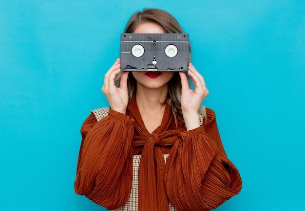 Jeune femme avec cassette vhs sur bleu