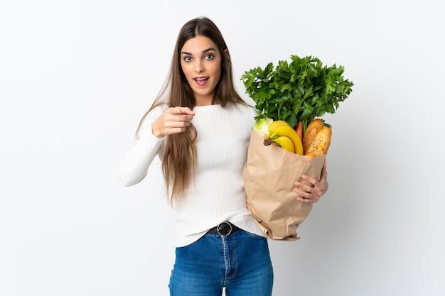 Jeune femme caucasienne, acheter de la nourriture isolé sur blanc surpris et pointant vers l'avant