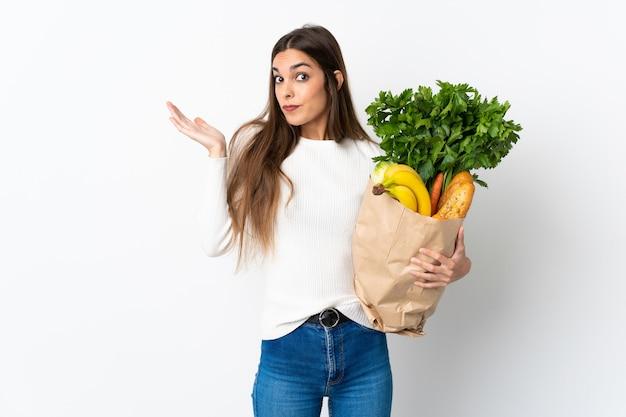 Jeune femme caucasienne, acheter de la nourriture isolé sur fond blanc ayant des doutes tout en levant les mains