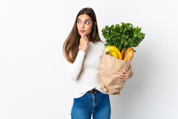 Jeune femme caucasienne, acheter de la nourriture isolée sur blanc ayant des doutes