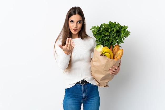 Jeune femme caucasienne, acheter de la nourriture isolée sur blanc invitant à venir avec la main. heureux que tu sois venu