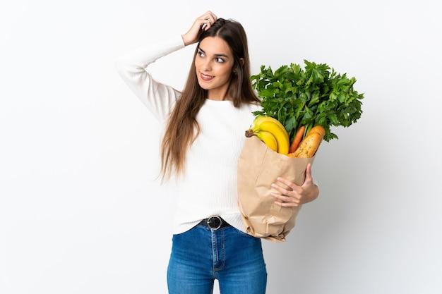 Jeune femme caucasienne, acheter de la nourriture isolée sur blanc souriant beaucoup