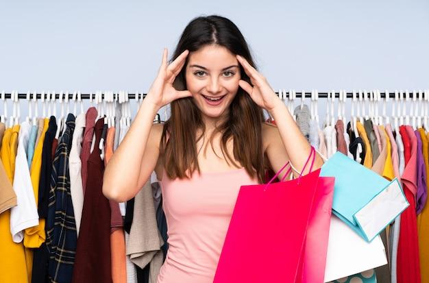 Jeune femme caucasienne, acheter des vêtements dans un magasin avec une expression surprise
