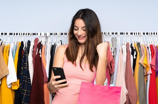 Jeune femme caucasienne, acheter des vêtements dans un magasin avec téléphone en position de victoire