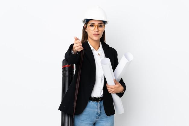 Jeune femme caucasienne architecte avec casque et tenant des plans