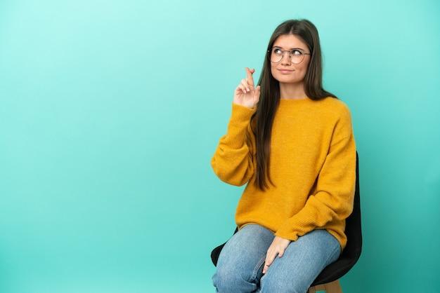 Jeune femme caucasienne assise sur une chaise isolée sur fond bleu avec les doigts croisés et souhaitant le meilleur