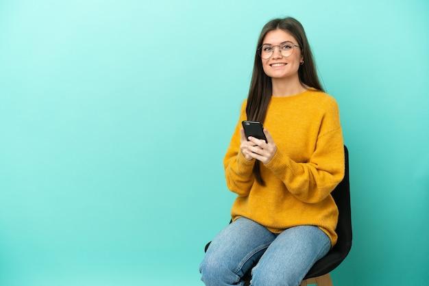 Jeune femme caucasienne assise sur une chaise isolée sur fond bleu envoyant un message avec le mobile