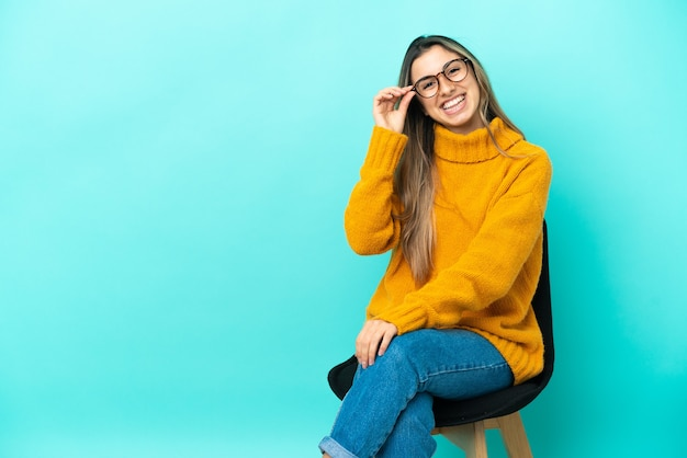 Jeune femme caucasienne assise sur une chaise isolée sur fond bleu avec des lunettes et heureuse