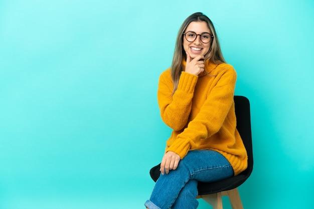 Jeune femme caucasienne assise sur une chaise isolée sur fond bleu avec des lunettes et souriant