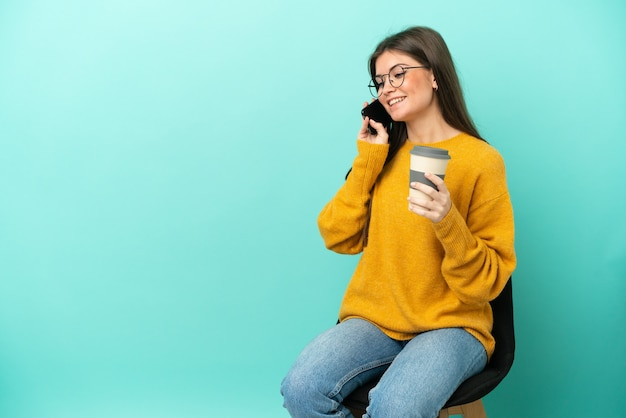 Jeune femme caucasienne assise sur une chaise isolée sur fond bleu tenant du café à emporter et un mobile