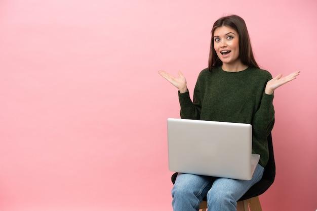 Jeune femme caucasienne assise sur une chaise avec son ordinateur portable isolé sur fond rose avec une expression faciale choquée