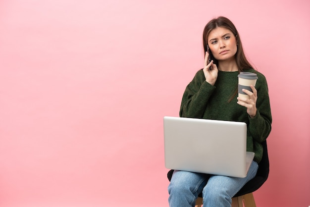 Jeune femme caucasienne assise sur une chaise avec son ordinateur portable isolé sur fond rose tenant du café à emporter et un mobile