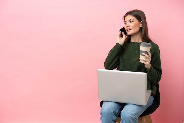 Jeune femme caucasienne assise sur une chaise avec son ordinateur portable isolé tenant du café à emporter et un mobile