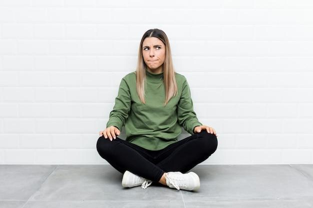 Jeune femme caucasienne assise sur le sol confuse, se sent douteuse et incertaine.