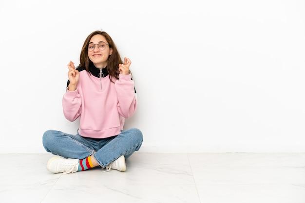 Jeune femme caucasienne assise sur le sol isolé sur fond blanc avec les doigts qui se croisent