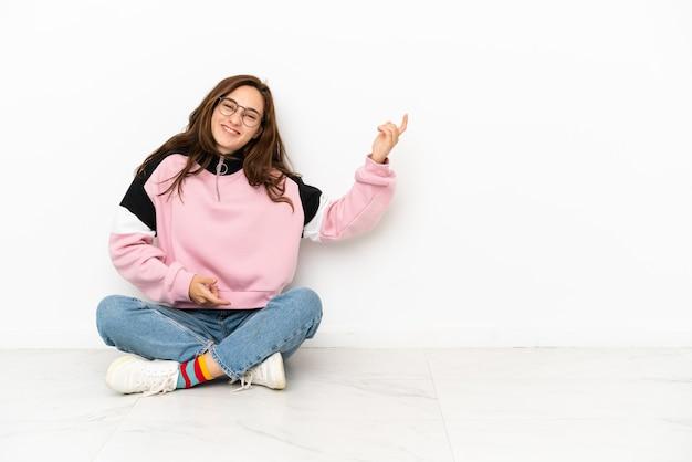 Jeune femme caucasienne assise sur le sol isolé sur fond blanc faisant un geste de guitare