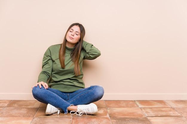 Jeune femme caucasienne assise sur le sol isolé souffrant de douleurs au cou en raison d'un mode de vie sédentaire.