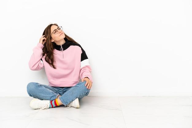 Jeune femme caucasienne assise sur le sol isolée sur fond blanc ayant des doutes et avec une expression de visage confuse