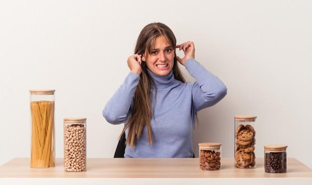 Jeune femme caucasienne assise à une table avec un pot de nourriture isolé sur fond blanc couvrant les oreilles avec les mains.