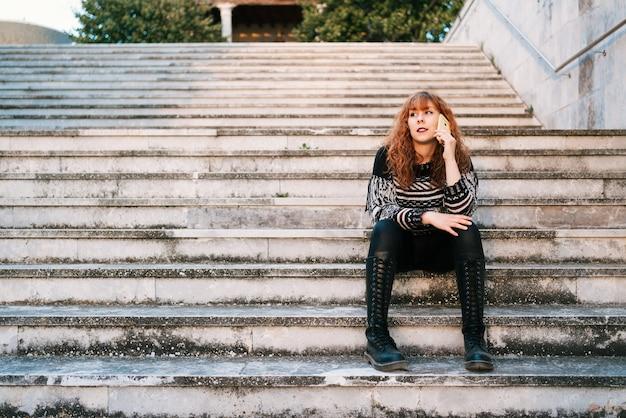 Jeune femme caucasienne aux cheveux roux parlant au téléphone assise sur les escaliers à l'extérieur
