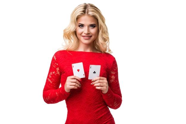 Jeune femme caucasienne aux longs cheveux blonds clairs en tenue de soirée tenant des cartes à jouer isolées p...