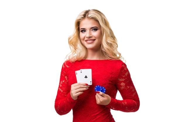 Jeune femme caucasienne aux longs cheveux blonds clairs en tenue de soirée tenant des cartes à jouer et des jetons. isolé sur fond blanc. poker