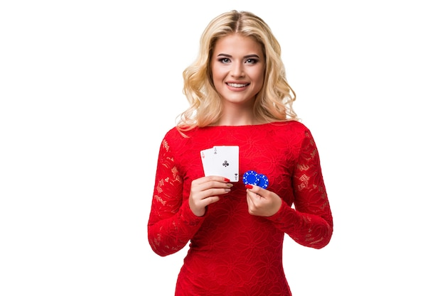 Jeune femme caucasienne aux longs cheveux blonds clairs en tenue de soirée tenant des cartes à jouer et des jetons. isolé. poker