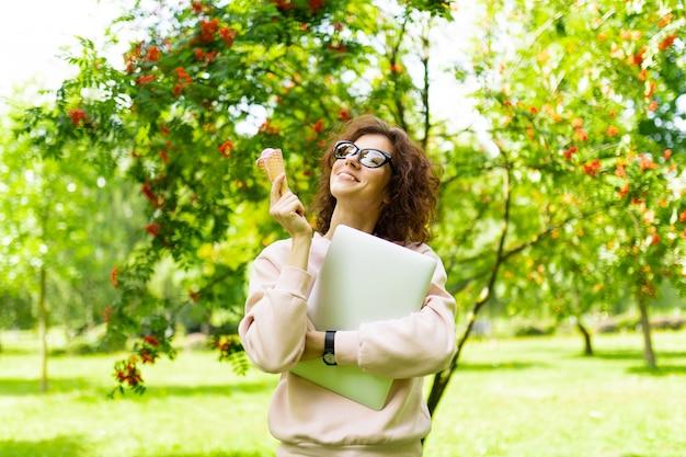 Jeune femme caucasienne aux yeux verts, sourire parfait, lèvres charnues, lunettes marche dans la nature, mange une glace, tient un ordinateur portable dans ses mains et sourit