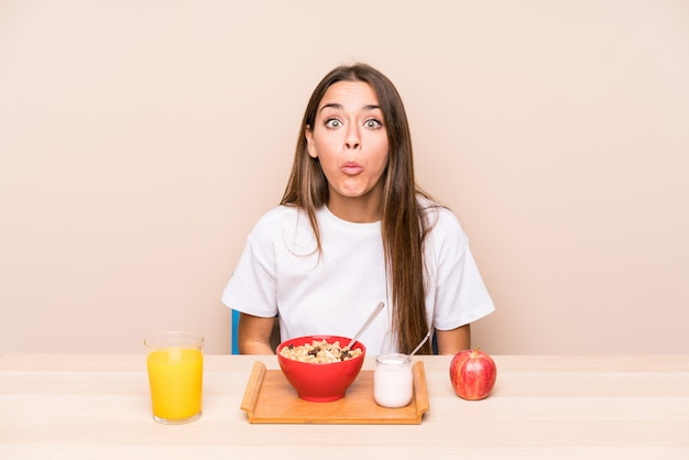Jeune femme caucasienne ayant un petit déjeuner isolé hausse les épaules et les yeux ouverts confus.