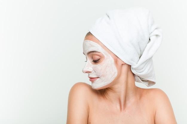 Jeune femme caucasienne, bénéficiant d'un traitement de masque facial