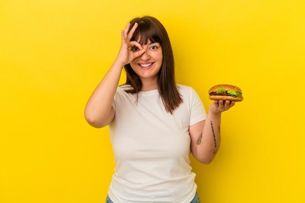 Jeune femme caucasienne bien roulée tenant un hamburger isolé sur fond jaune excité en gardant le geste ok sur les yeux.