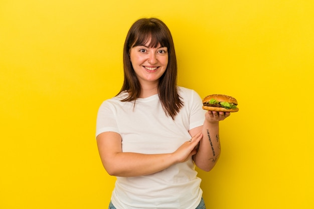 Jeune femme caucasienne bien roulée tenant un hamburger isolé sur fond jaune en riant et en s'amusant.