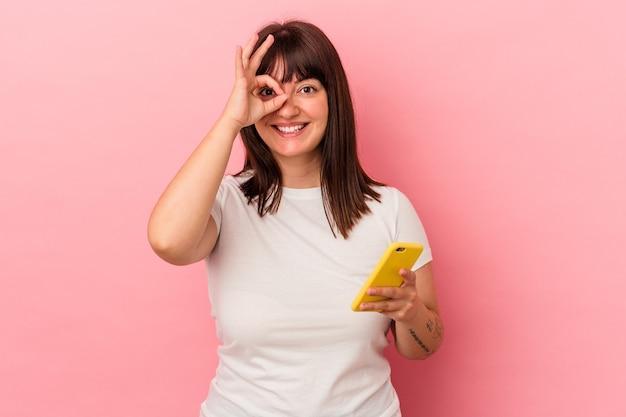 Jeune femme caucasienne bien roulée tenant un téléphone portable isolé sur fond rose excité en gardant le geste ok sur les yeux.