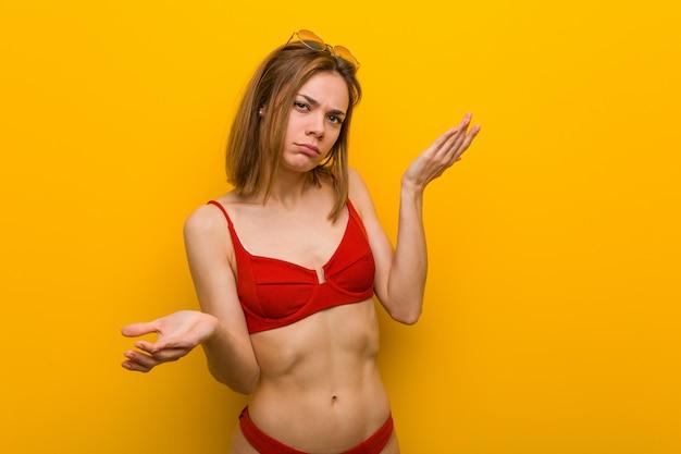 Jeune femme caucasienne, bikini et lunettes de soleil doutant entre deux options.