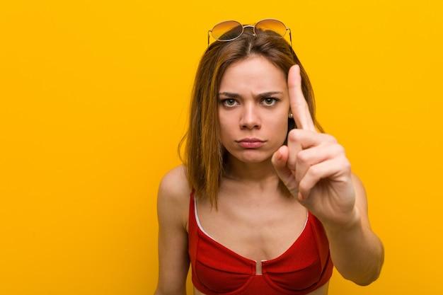 Jeune femme caucasienne, bikini et lunettes de soleil montrant le numéro un avec le doigt.
