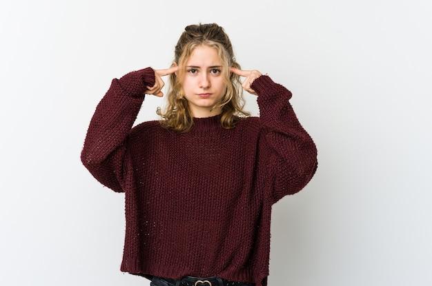 Jeune femme caucasienne sur blanc concentré sur une tâche, gardant l'index pointant la tête.