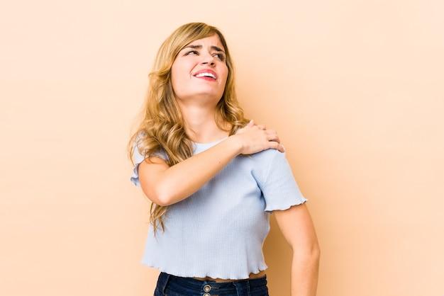 Jeune femme caucasienne blonde ayant une douleur à l'épaule.