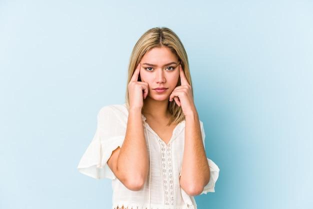 Jeune femme caucasienne blonde isolée concentrée sur une tâche, gardant l'index pointant la tête.