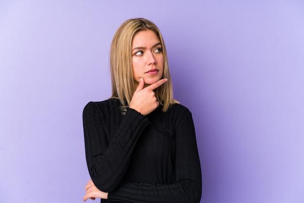 Jeune femme caucasienne blonde isolée en contemplant, planifier une stratégie, penser à la manière d'une entreprise.