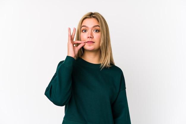 Jeune femme caucasienne blonde isolée avec les doigts sur les lèvres en gardant un secret.