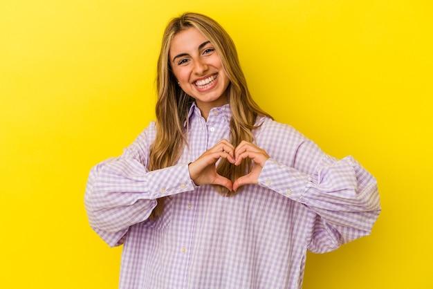 Jeune femme caucasienne blonde isolée sur fond jaune souriant et montrant une forme de coeur avec les mains.