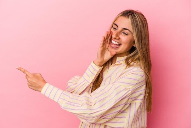 Jeune femme caucasienne blonde isolée sur fond rose disant un potin, pointant vers le côté rapportant quelque chose.