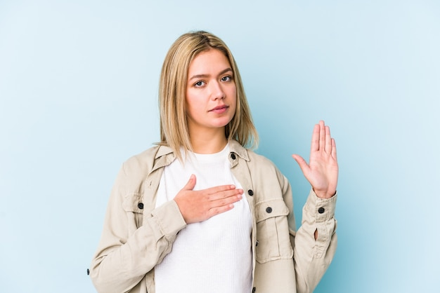Jeune femme caucasienne blonde isolée en prêtant serment, mettant la main sur la poitrine.