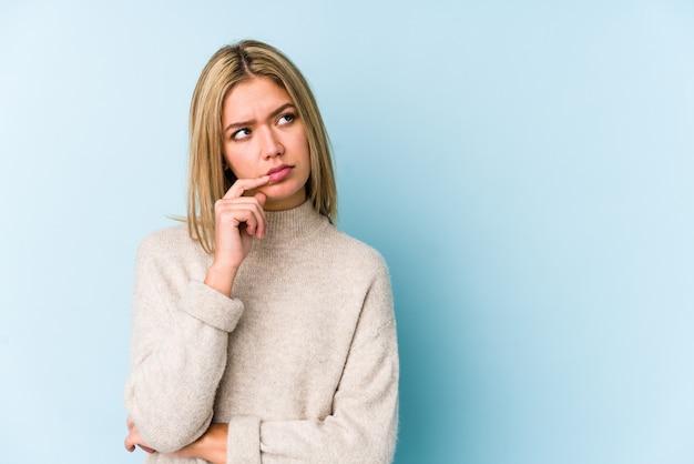 Jeune femme caucasienne blonde isolée à la recherche de côté avec une expression douteuse et sceptique.