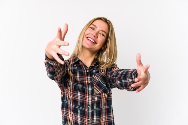 Jeune femme caucasienne blonde isolée se sent confiante en donnant un câlin à la caméra.