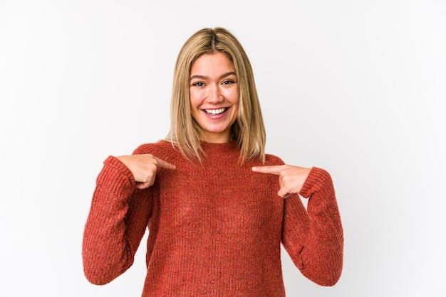 Jeune femme caucasienne blonde isolée surprise pointant avec le doigt, souriant largement.