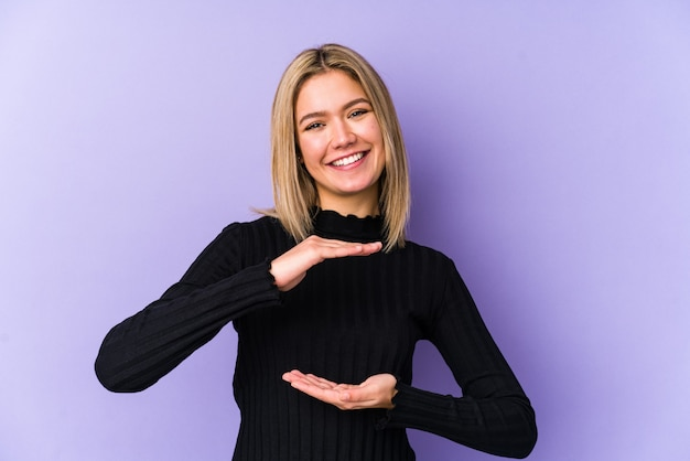 Jeune femme caucasienne blonde isolée tenant quelque chose à deux mains, présentation du produit.